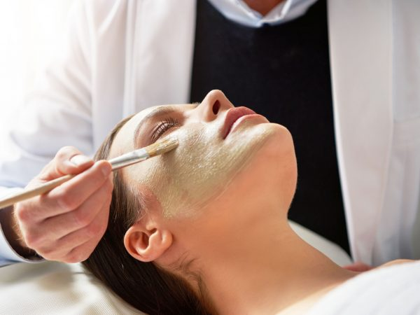 Unrecognizable male beautician putting mask on female face lying with eyes closed with brush in salon.