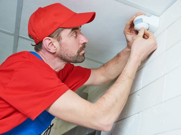 motion sensor or movement detector installation or adjustment by construction worker on the ceiling