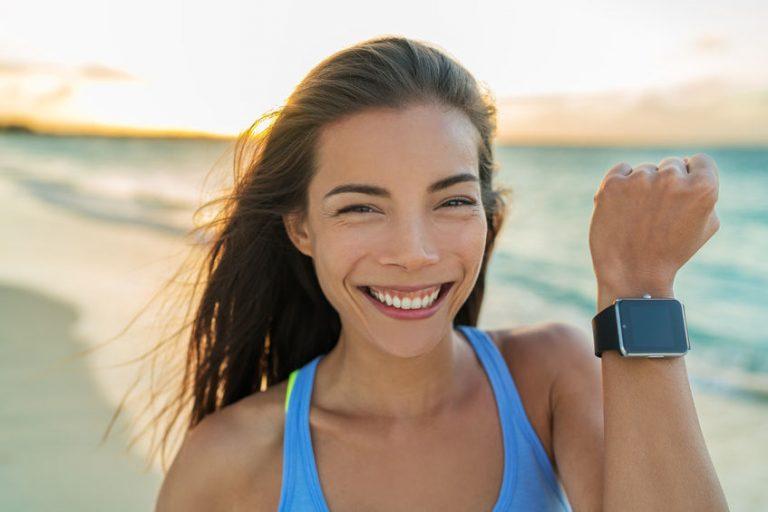 Donna sulla spiaggia con smartwatch