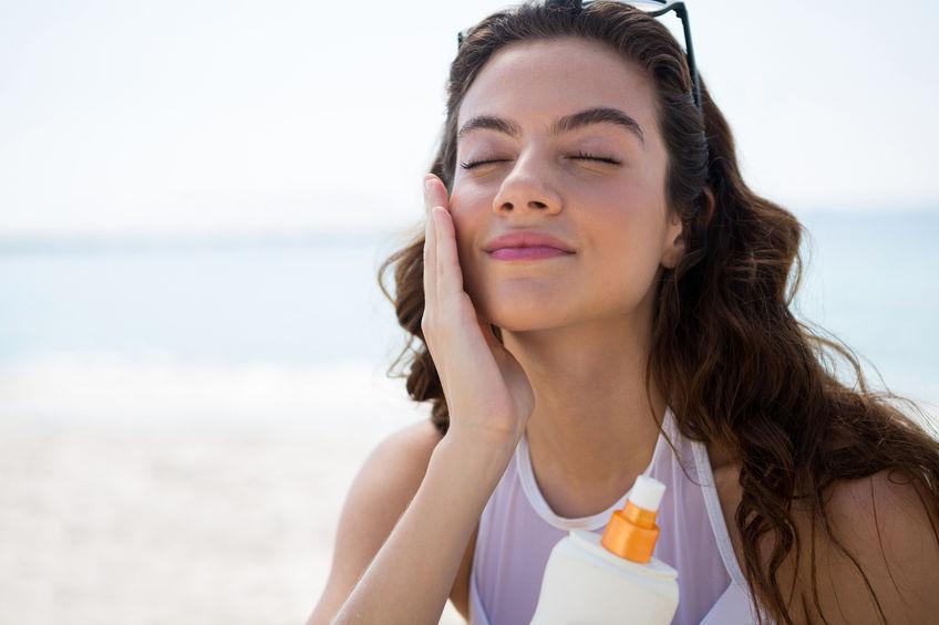 Donna che applica protezione solare facciale