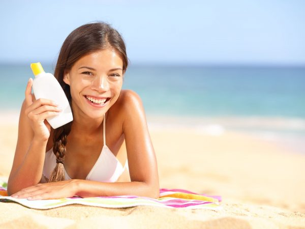 19808577 – sunscreen woman showing suntan lotion bottle. beautiful smiling happy asian woman with suntan cream in plastic container lying on beach during summer travel vacation. mixed race female model.