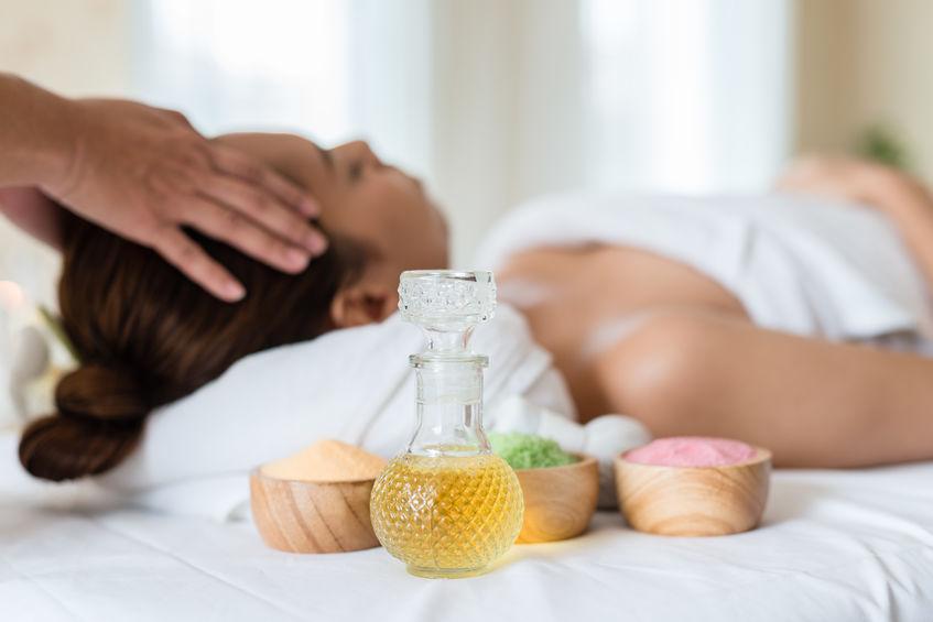 Immagine di un contenitore con olio, sullo sfondo una donna che riceve un massaggio