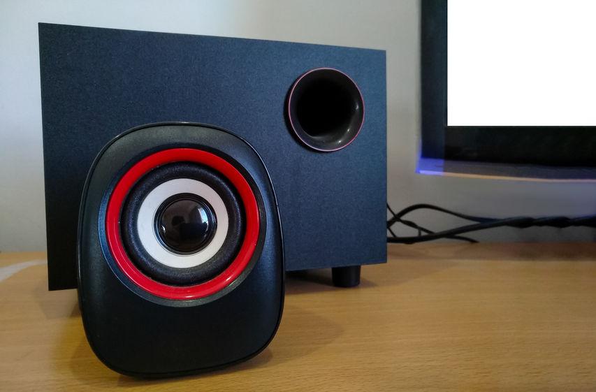 Altoparlante per PC e amplificatore sul tavolo con monitor