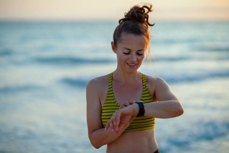 donna sulla spiaggia che esercita guardando l'orologio
