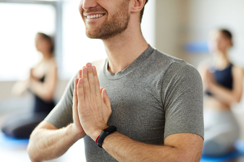 uomo che pratica yoga con smartband