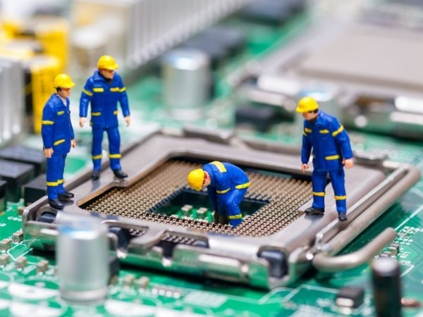 Group of construction workers repairing CPU. Technology concept