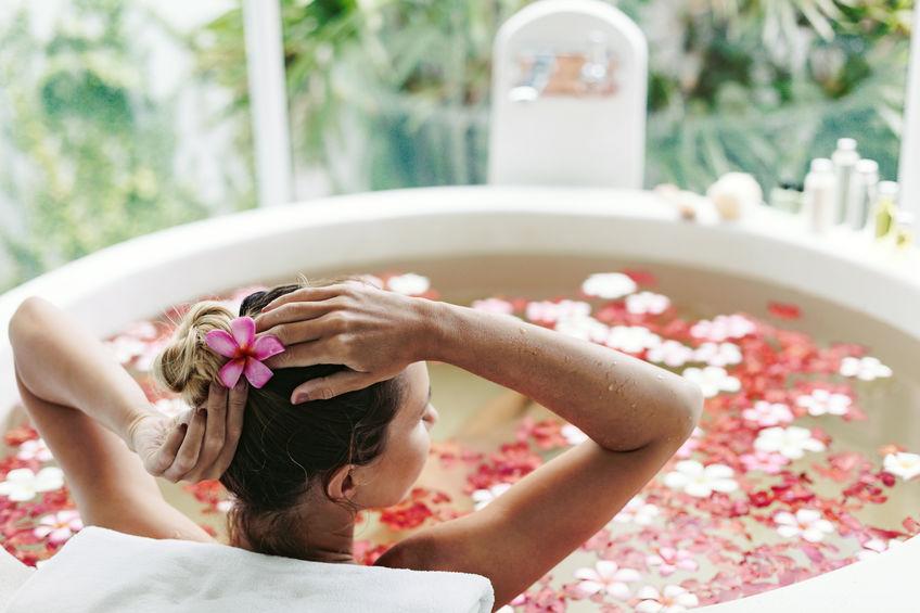 Donna nella vasca da bagno con petali di rose