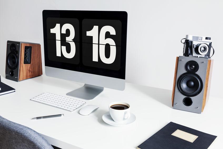 Primo piano di un'area di lavoro minimalista con un desktop computer e altoparlanti su una scrivania bianca in un interno moderno del Ministero degli Interni. Foto reale