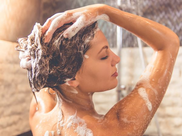 Beautiful naked young woman is smiling and using shampoo while taking shower in bathroom