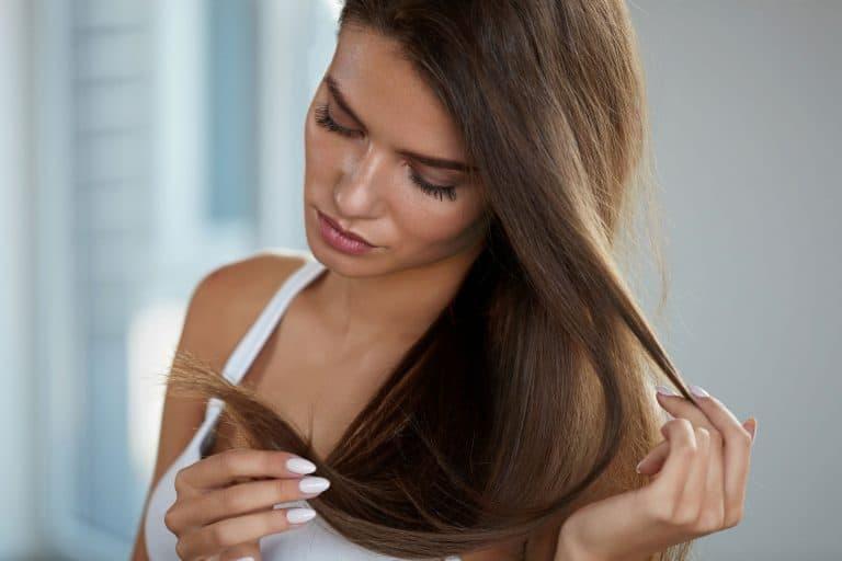 Donna che controlla le punte dei capelli