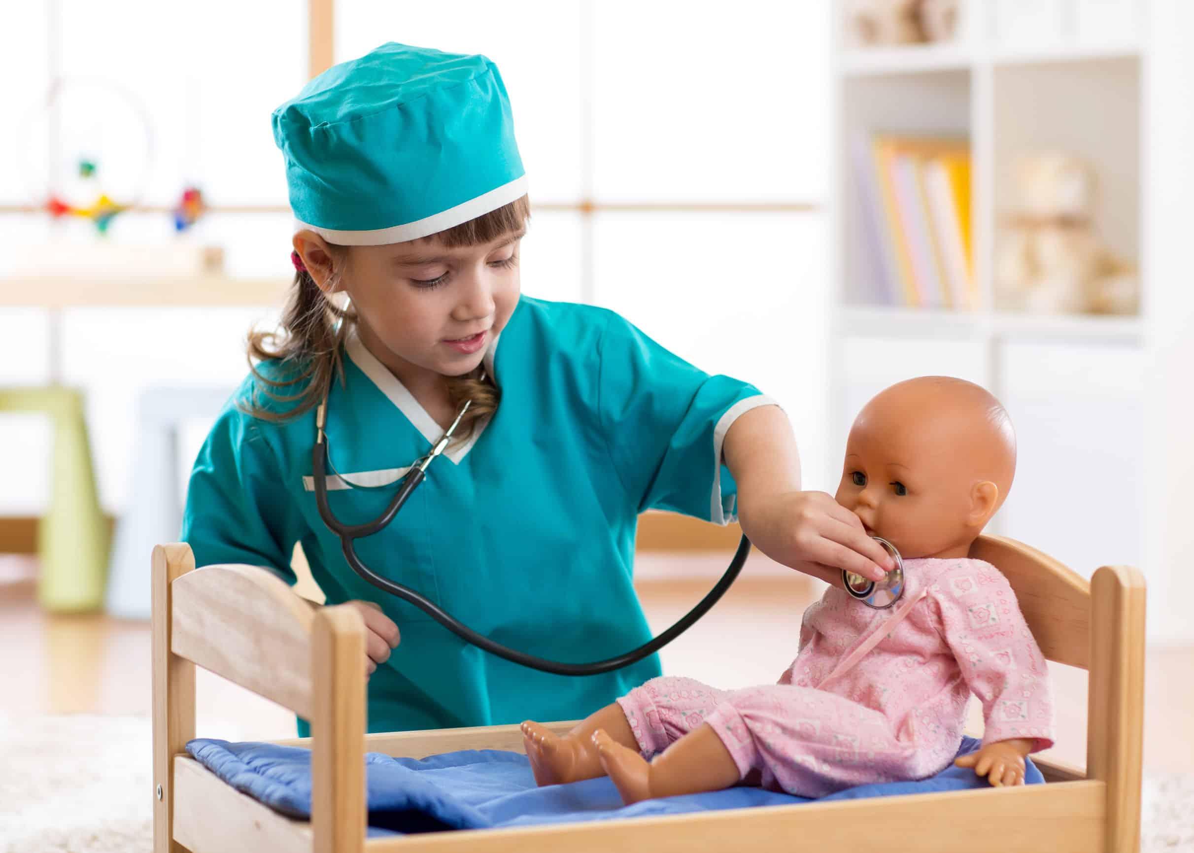 Bimba che gioca al dottore con la bambola