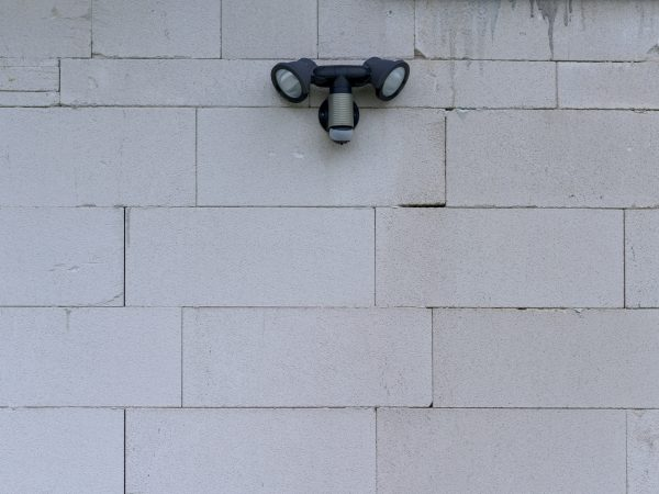 Two external security lights with motion sensor mounted on a cement brick wall with copy space below