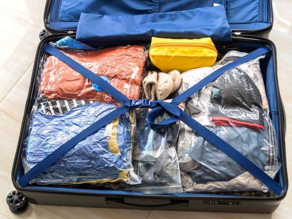 Valigia e vestiti nei sacchi sottovuoto