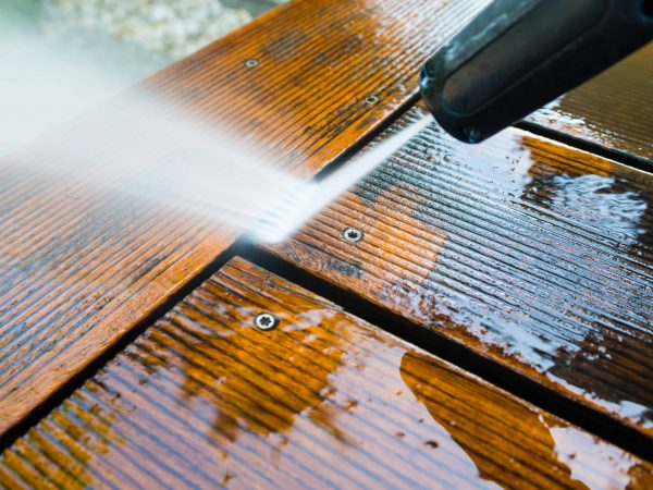 cleaning terrace with a power washer – high water pressure cleaner on wooden terrace surface