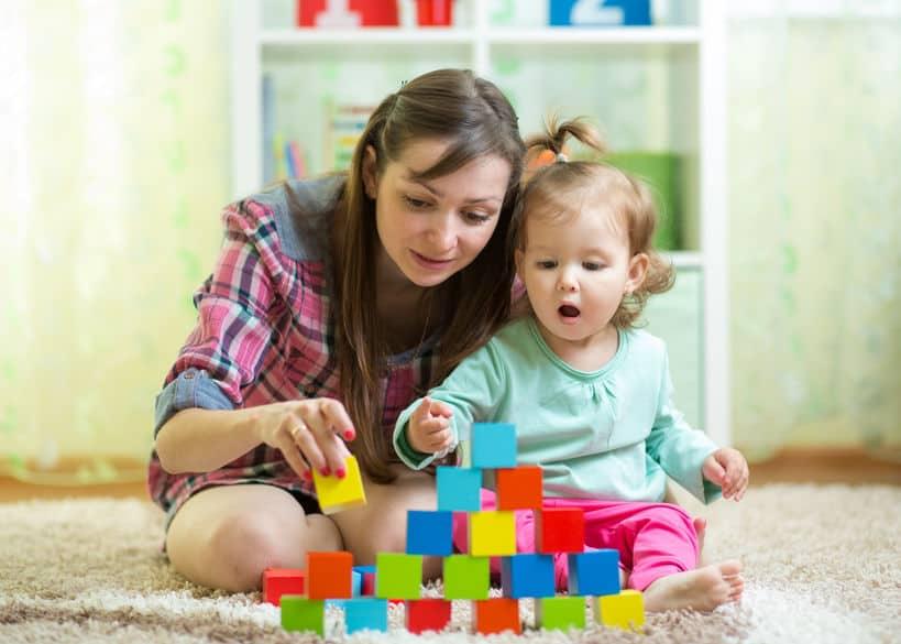 Mamma con figlia e blocchi di legno