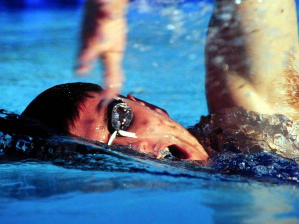 Uomo che nuota con occhialini svedesi