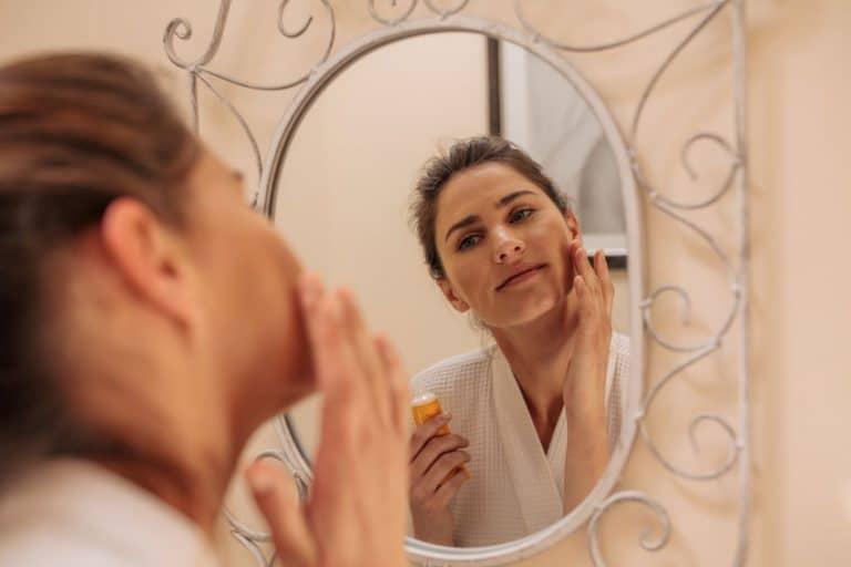 Donna che usa l'olio di ricino sul viso