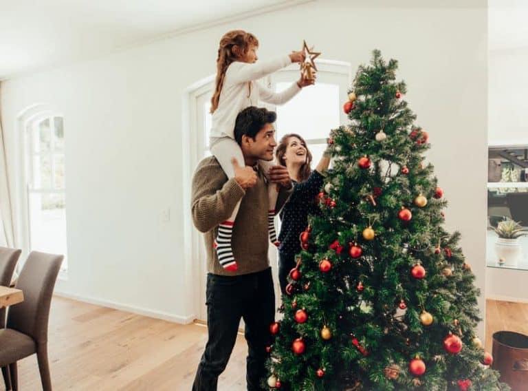 Famiglia che addobba l'albero di Natale