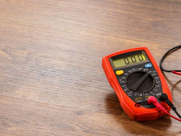 Multimeter measuring device electric tool for measurement of voltage lying on wooden floor background