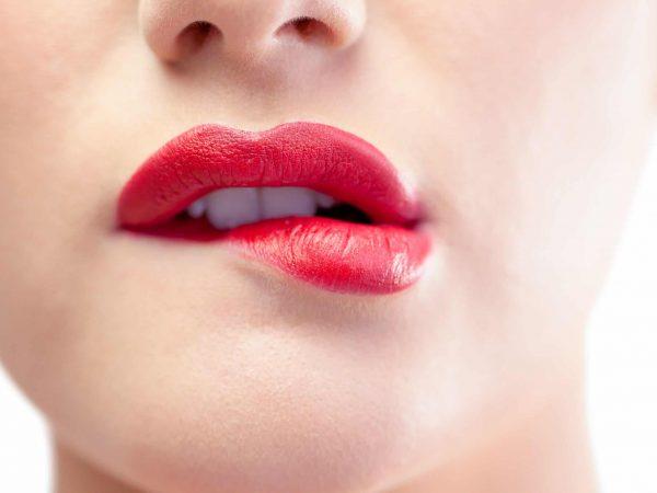 Donna con rossetto rosso che si morde il labbro