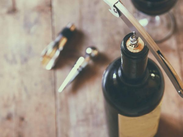 56812803 – top view image of red wine bottle and corkscrew over wooden table. retro style image selective focus.