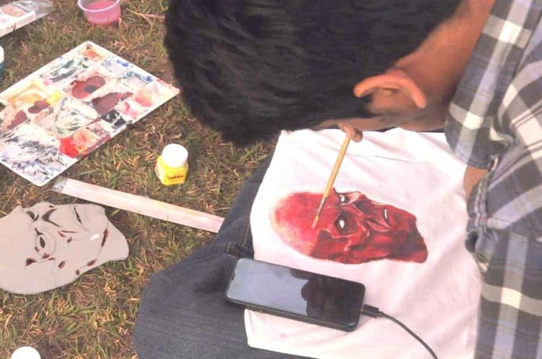 Uomo che usa colori per tessuti su una maglietta