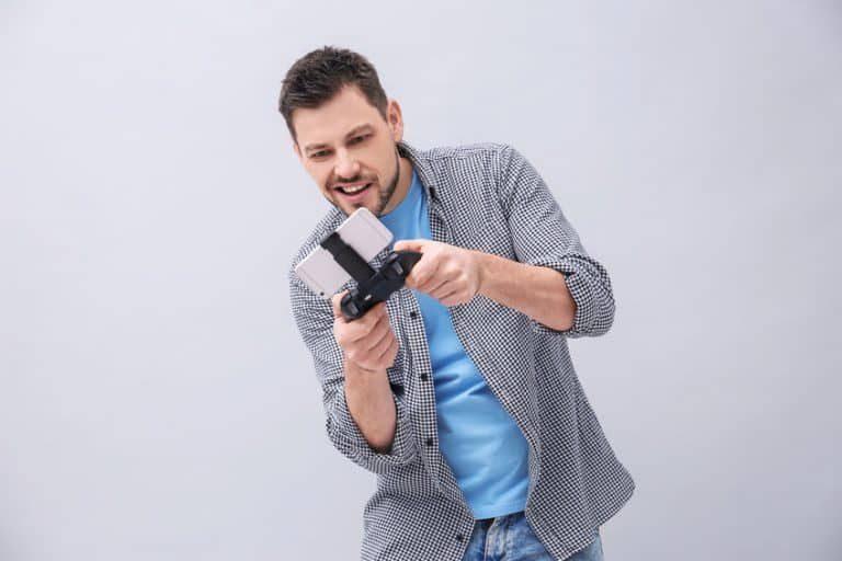 Uomo che gioca con controller per smartphone