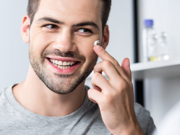 happy man applying facial cream in bathroom while looking at mirror
