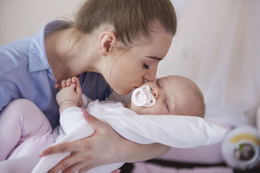 Mamma che bacio il neonato sul cuscino