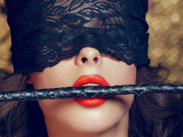 Donna bendata con frustino in bocca
