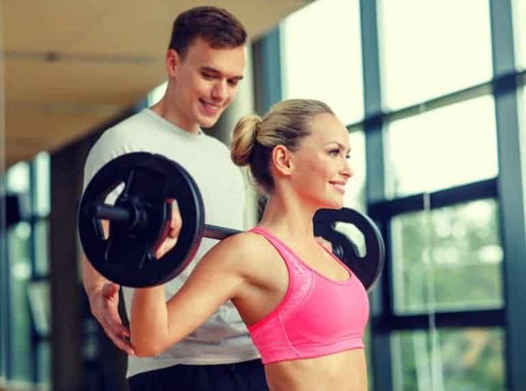 Donna che si allena con bilanciere e pesi