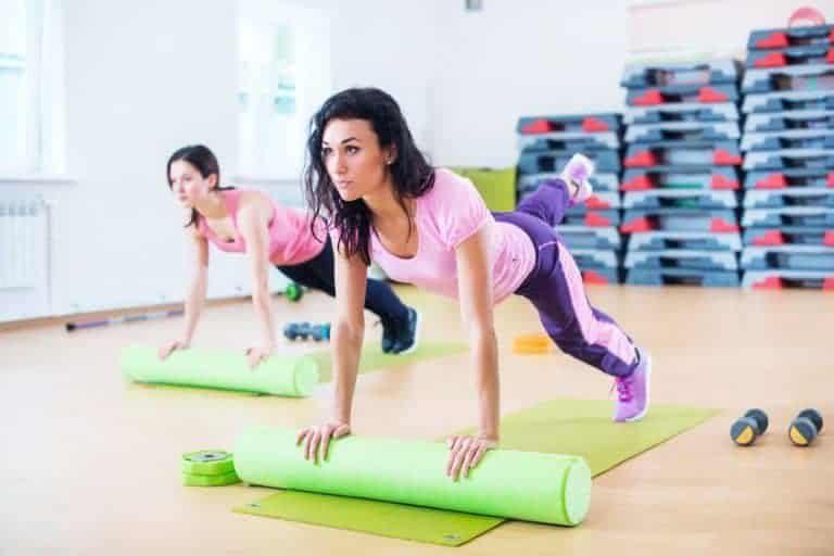 Donne che usano il foam roller per fare ginnastica