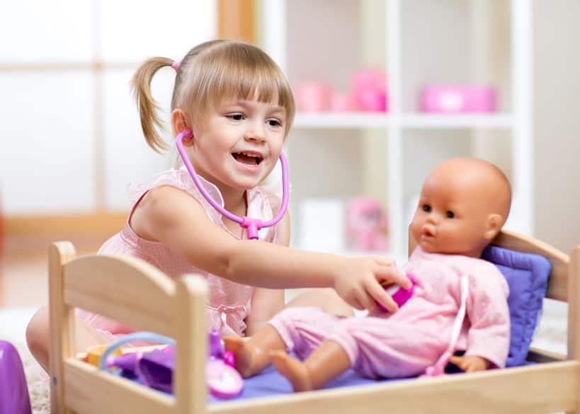 Bambina che ausculta bambola
