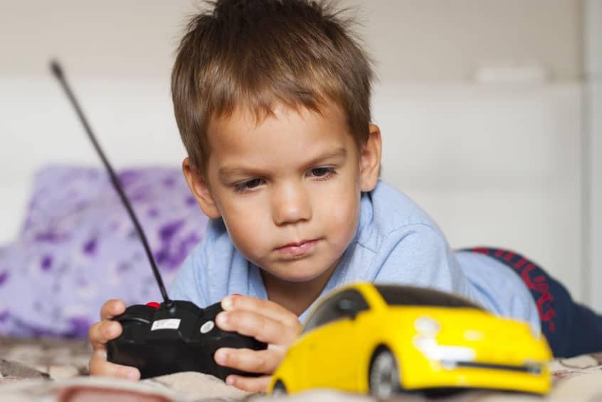 Bambino che gioca con macchinina telecomandata