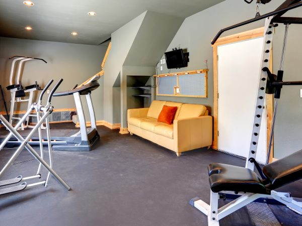 Grey walls gym room with window. View of exercise equipments and yellow couch