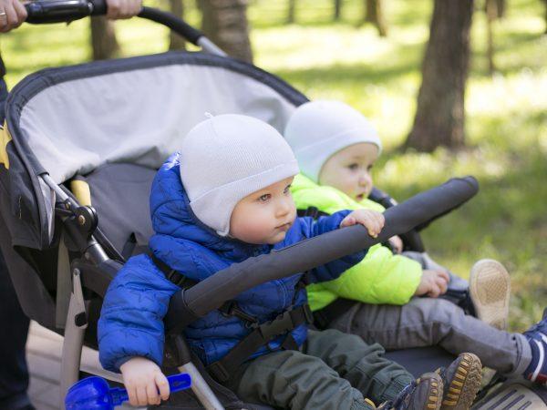 Bambini dentro un passeggino da corsa