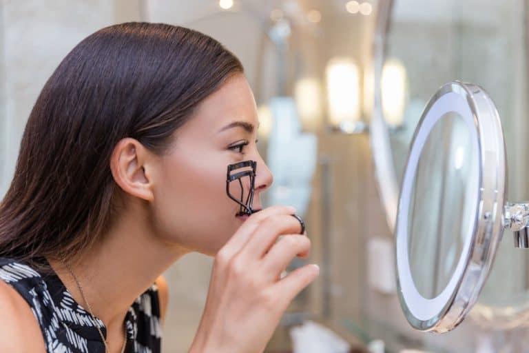 Donna con piegaciglia allo specchio