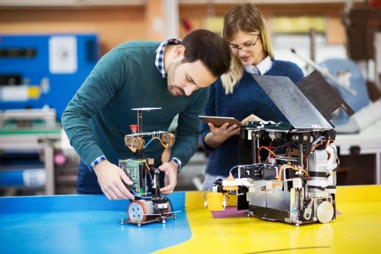 Due persone che lavorano con parti elettroniche
