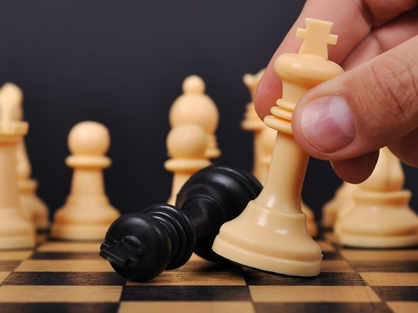 White Chess King makes a checkmate Black King on chessboard
