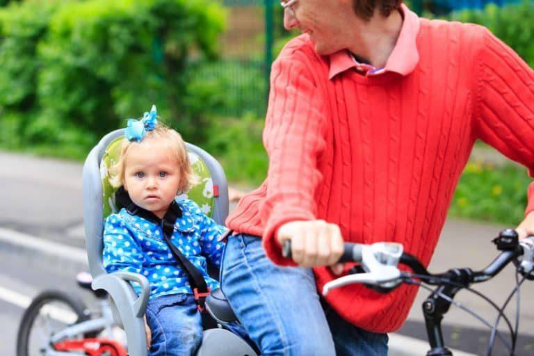 Bambina nel seggiolino per bicicletta