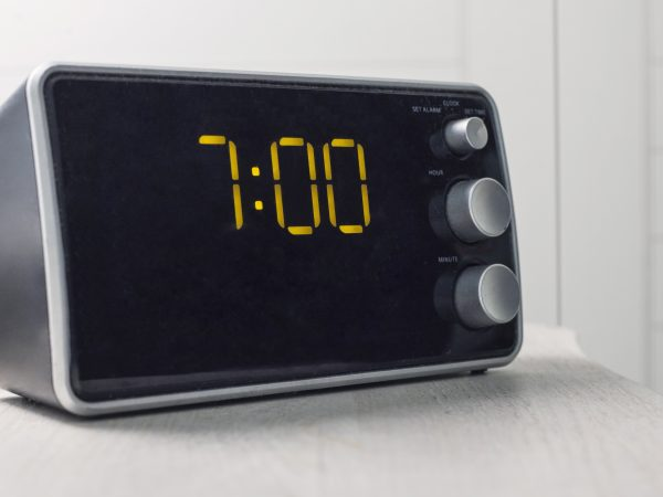 Digital alarm clock with yellow digits showing seven oclock