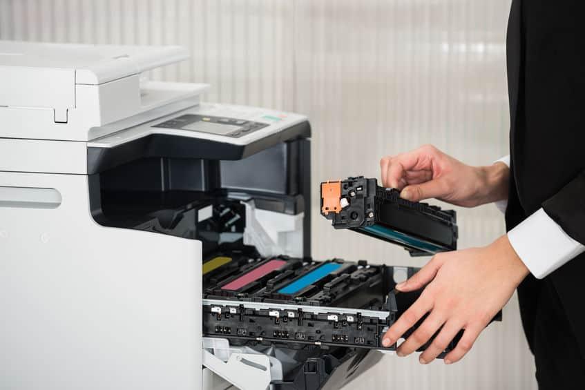 Una persona che cambia il toner alla stampante