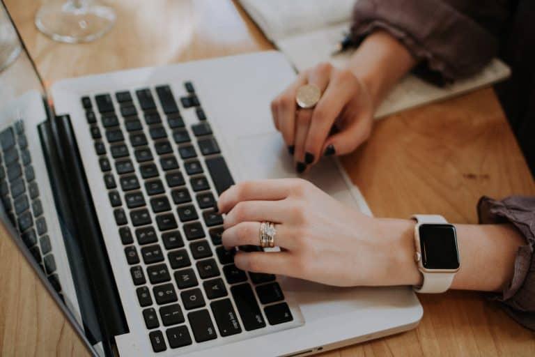 Donna al computer con lo smartwatch al polso