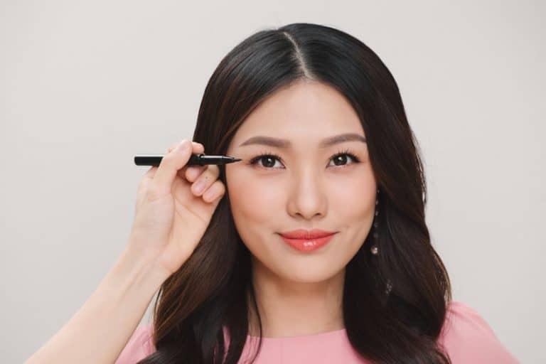 Donna a cui applicano l'eyeliner