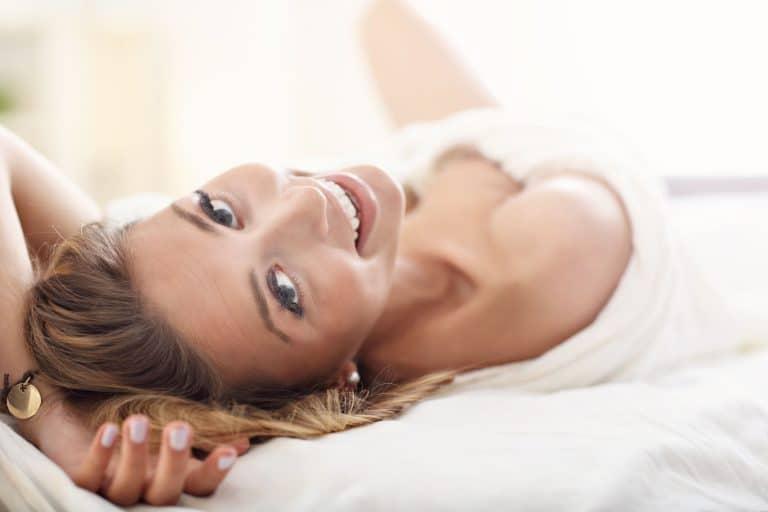 Donna stesa sul letto che sorride