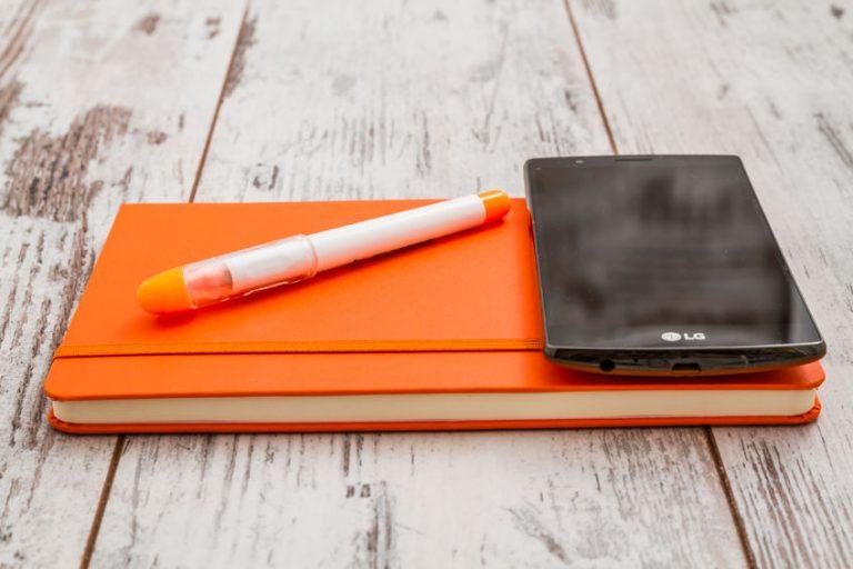 Smartphone LG sopra un'agendina aranciione