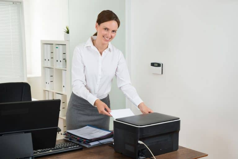 Donna che usa una stampante in ufficio