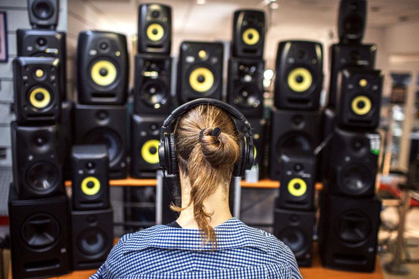 Donna davanti a tante casse audio