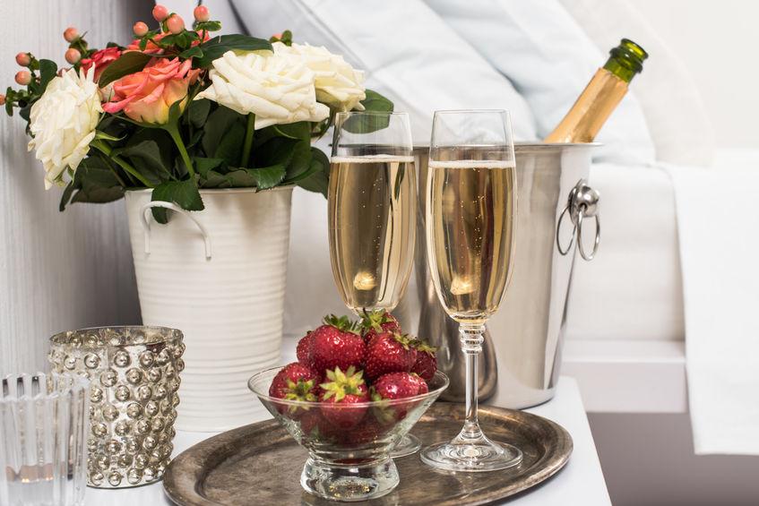 Champagne a letto in una camera d'albergo, secchiello per il ghiaccio, bicchieri e frutta su lino bianco