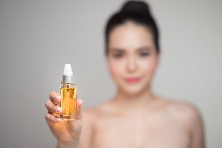 Modelo mostrando aceite para cabello en envase de vidrio
